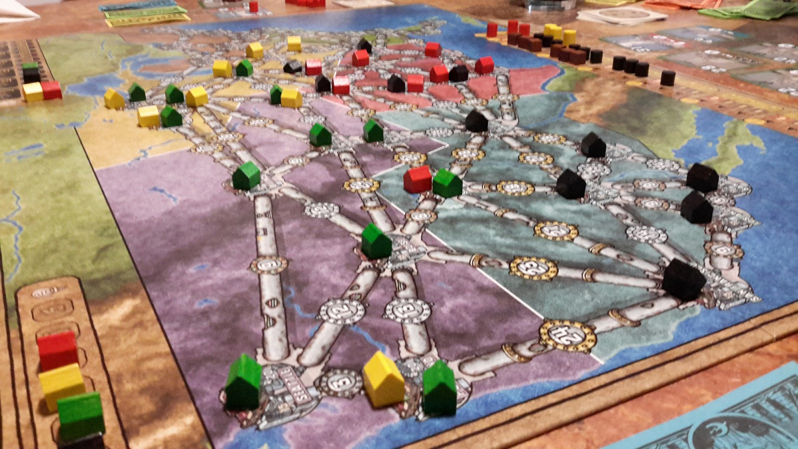 A game of Power Grid mid game, the board is littered with wooden houses.