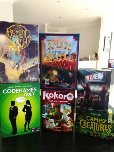 Board games stacked on top of one another; Beyond Baker Street, Codenames Duet, Leaders of Euphoria, Kokoro, Pit Crew, and Campy Creatures