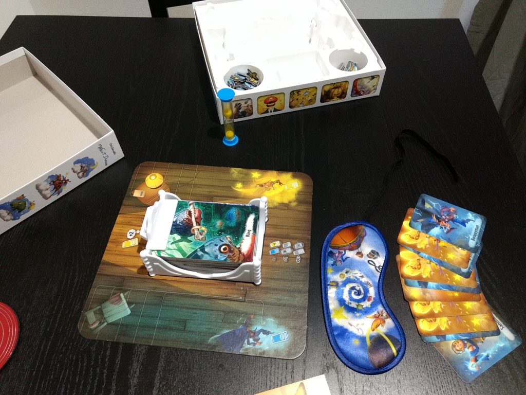 All components of the game are on display, sleeping mask, cards, card holder in the shape of a bed