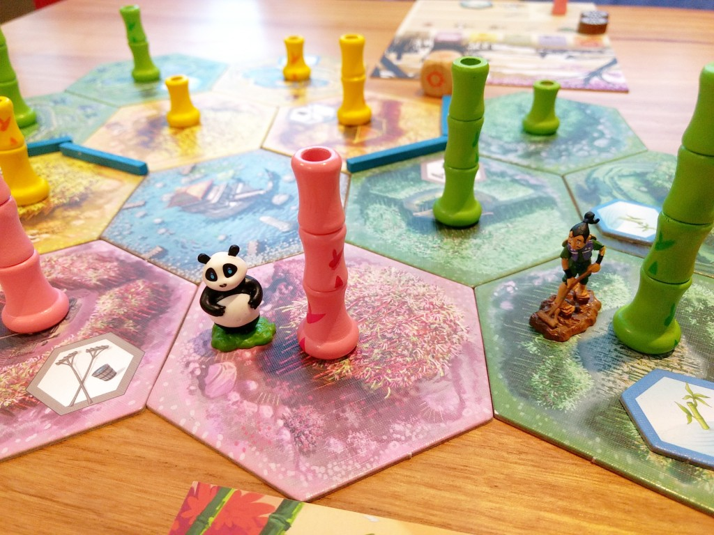 Takenoko mid game, the panda minature is standing next to a delicious pink bamboo stalk.