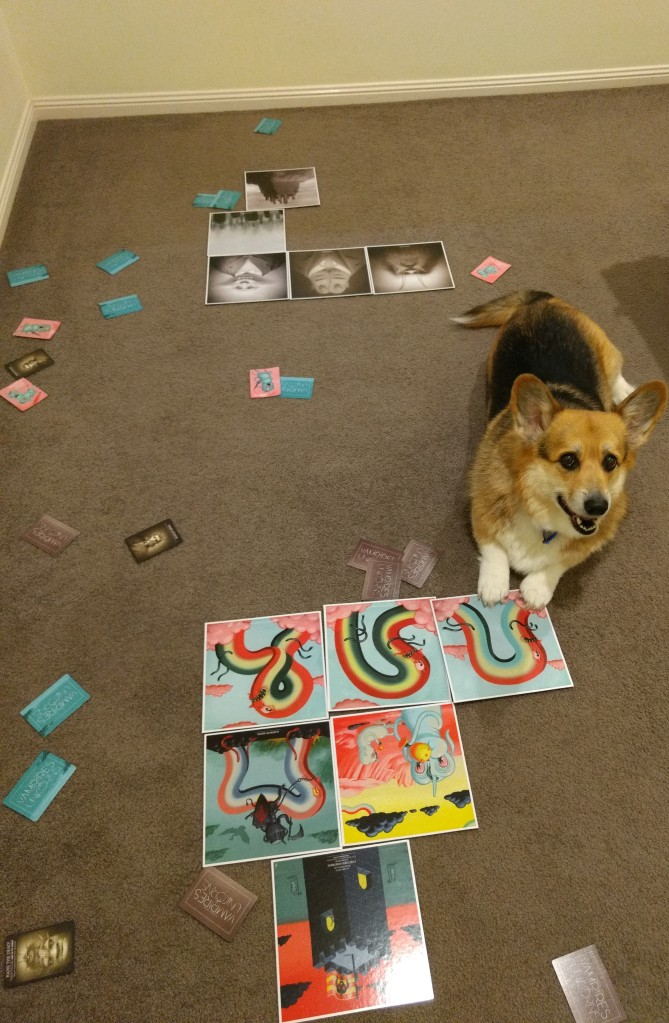 Middle of the game, cards are everywhere on the floor. Corgi has his cute paws on some game boards.