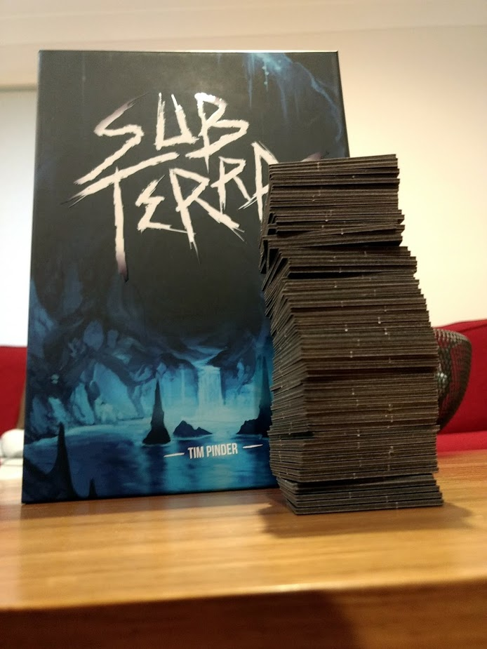 All of the tiles in Sub Terra stacked, with the box behind it. The stack goes 3/4 of the way up.