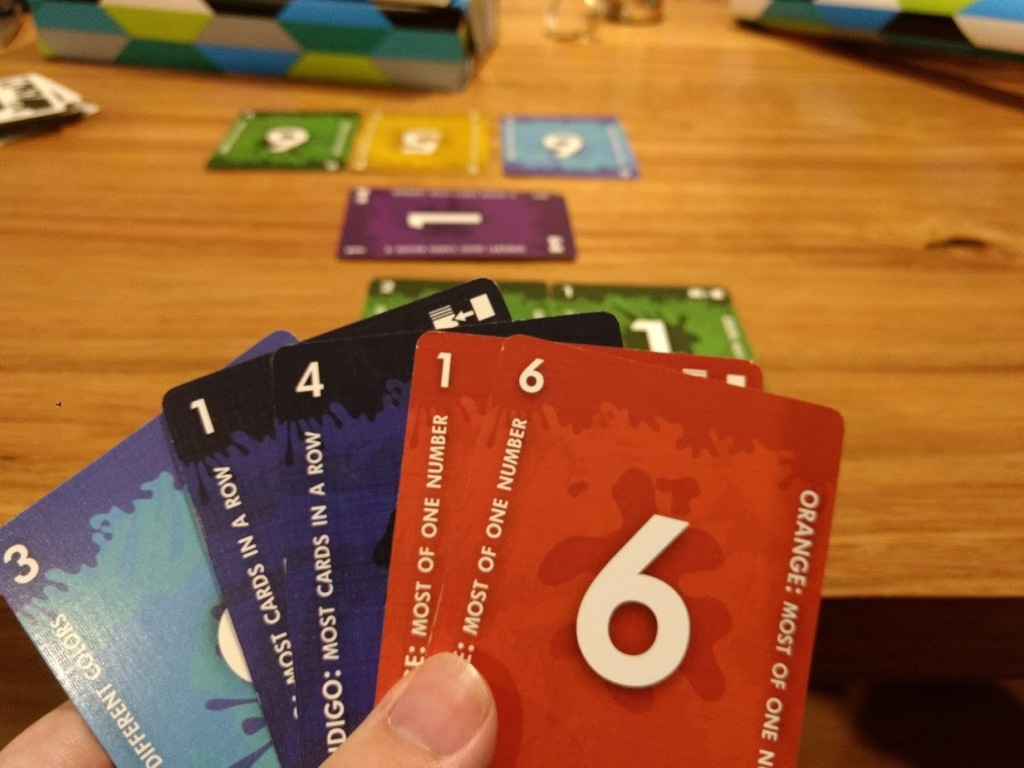A hand of coloured cards from Red7, rules down both sides, with a big number in the middle.