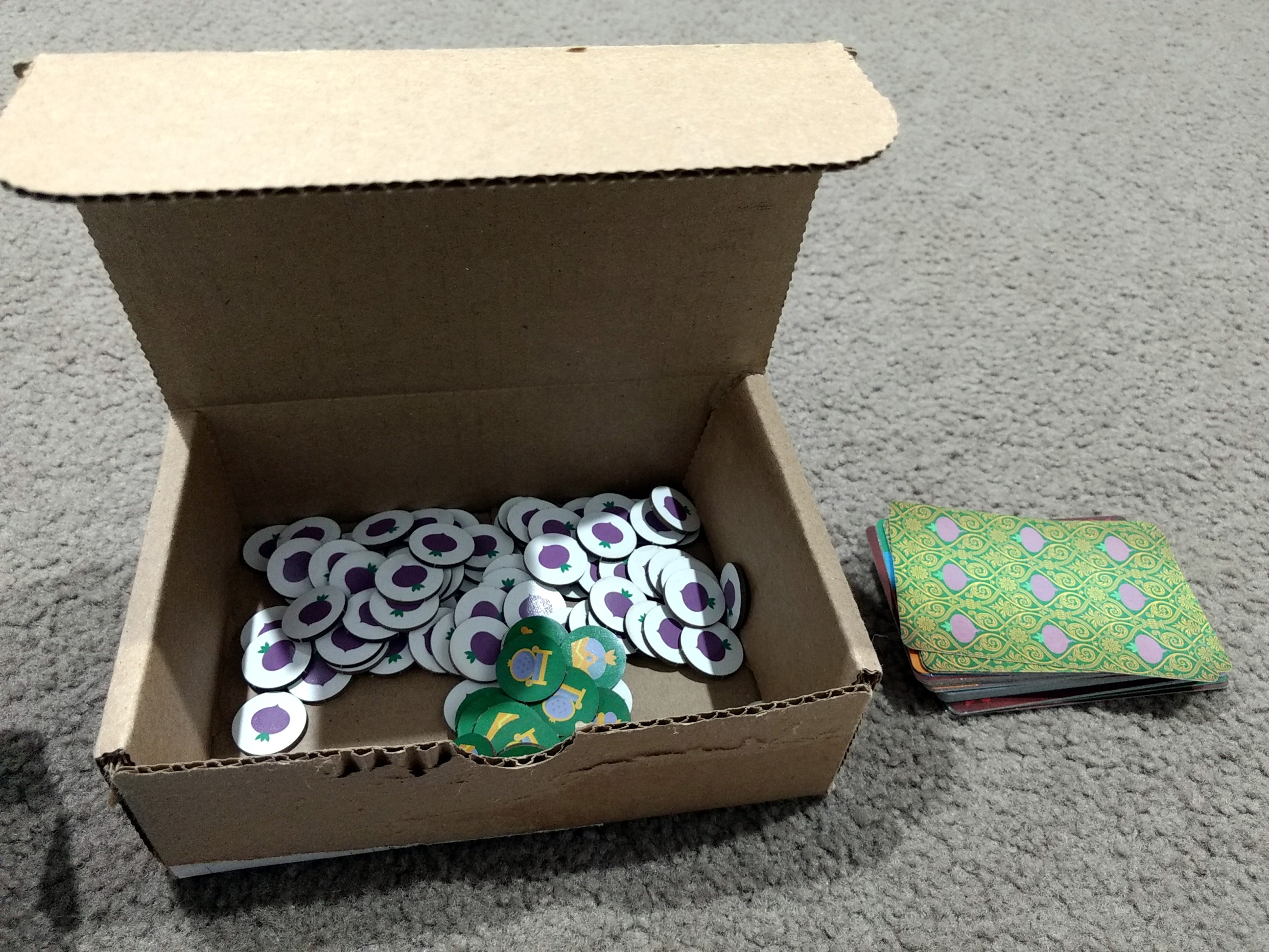 All components that come in Village Pillage. Turnip tokens, crown tokens, and a deck of cards.