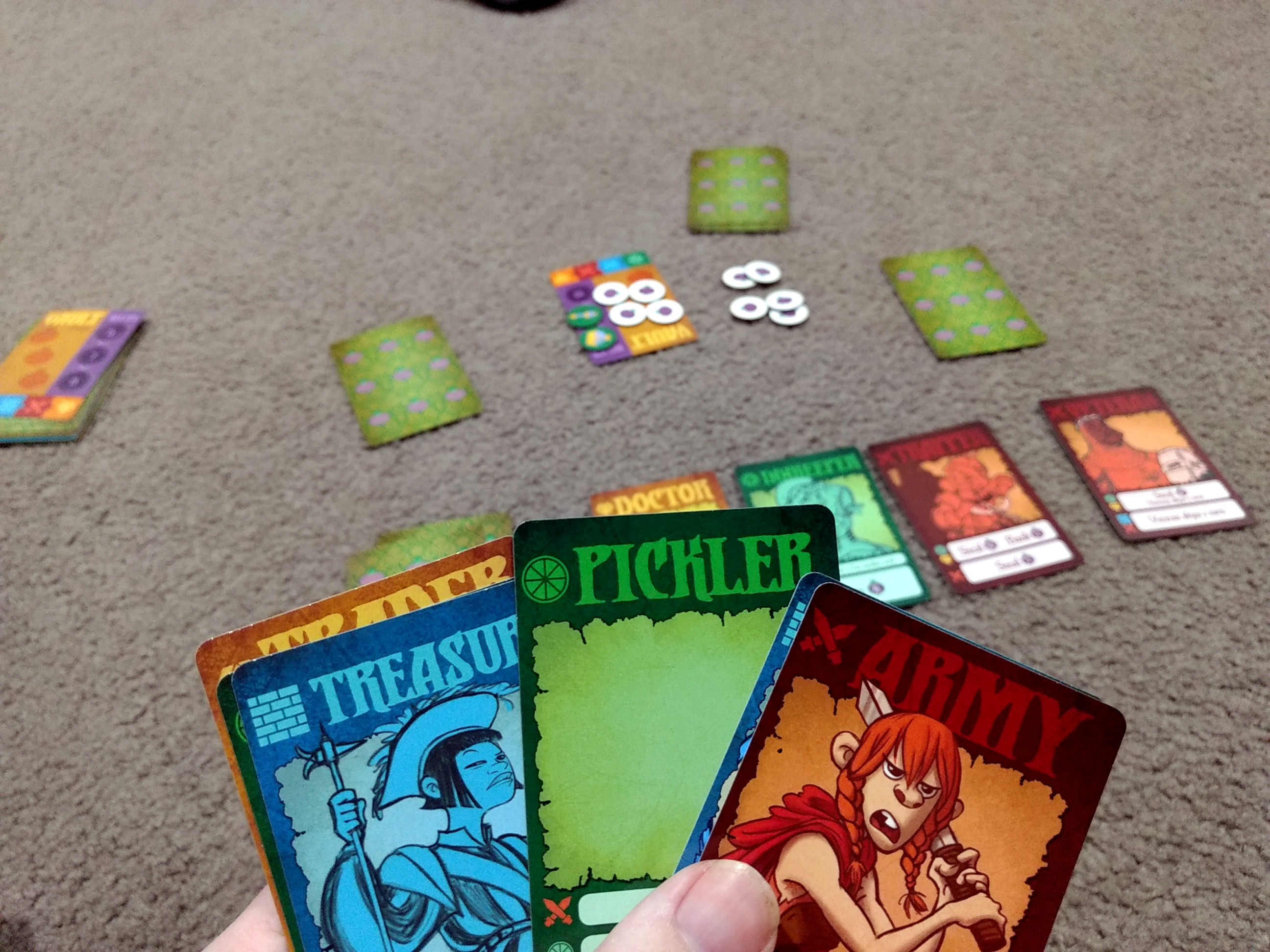 Village Pillage in play, a hand of cards that I'm holding, and in the background the market is displayed.