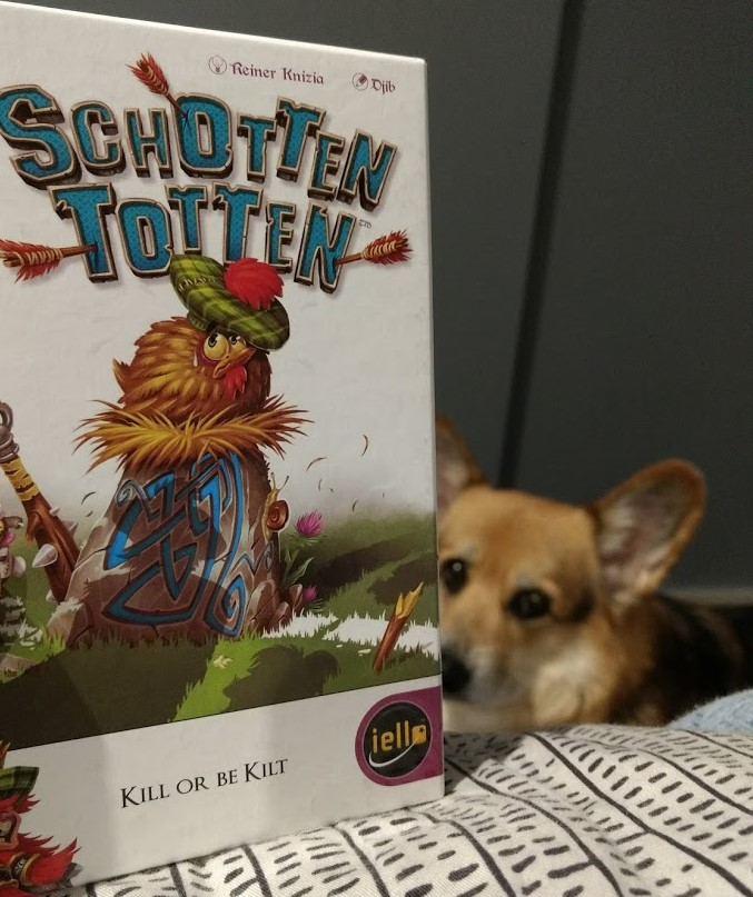 Up close shot of the Schotten Totten box with corgi looking on in the background.