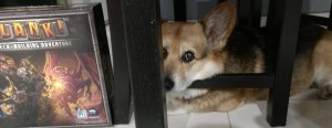 Corgi head on chair laying next to Clank box