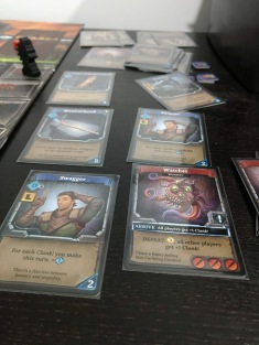 Cards from the board game Clank laid upon a black table