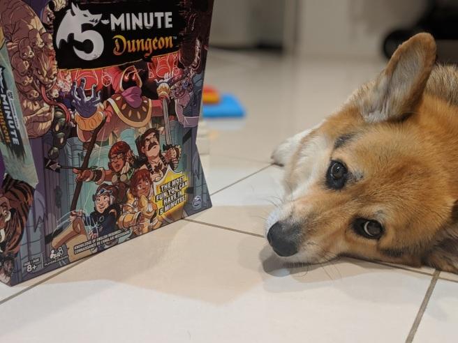 Incredibly cute corgi next to a board game box (5 minute dungeon