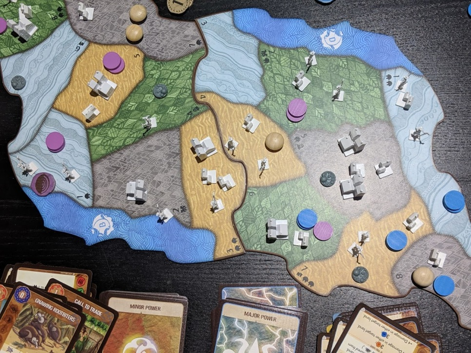 Overhead view of Spirit Island two player game. Sprawling plastic houses represent the invaders.