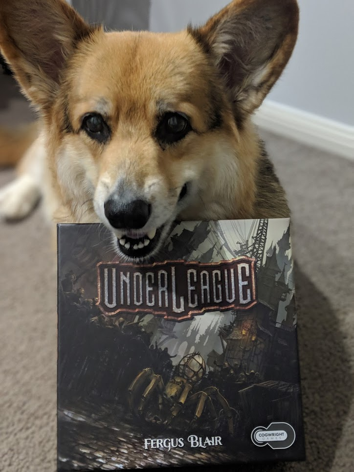 My cute corgi resting his chin on the box cover of Underleague.