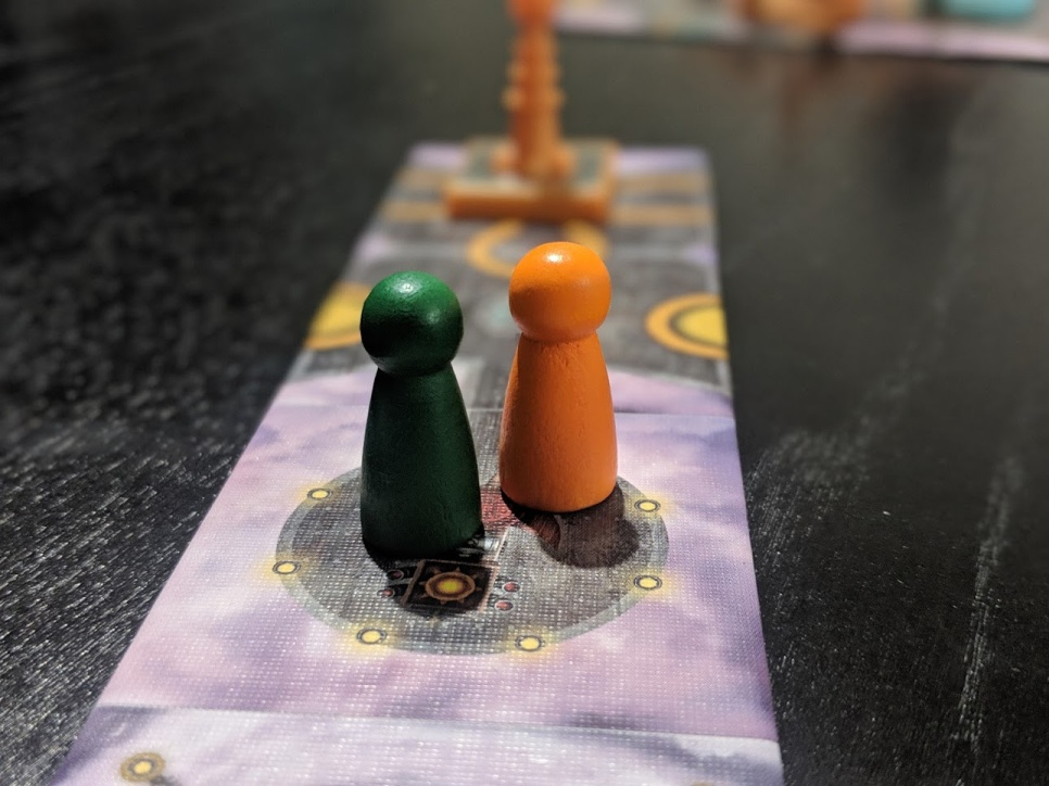 Two wooden tokens on the starting pad of Forbidden Sky.
