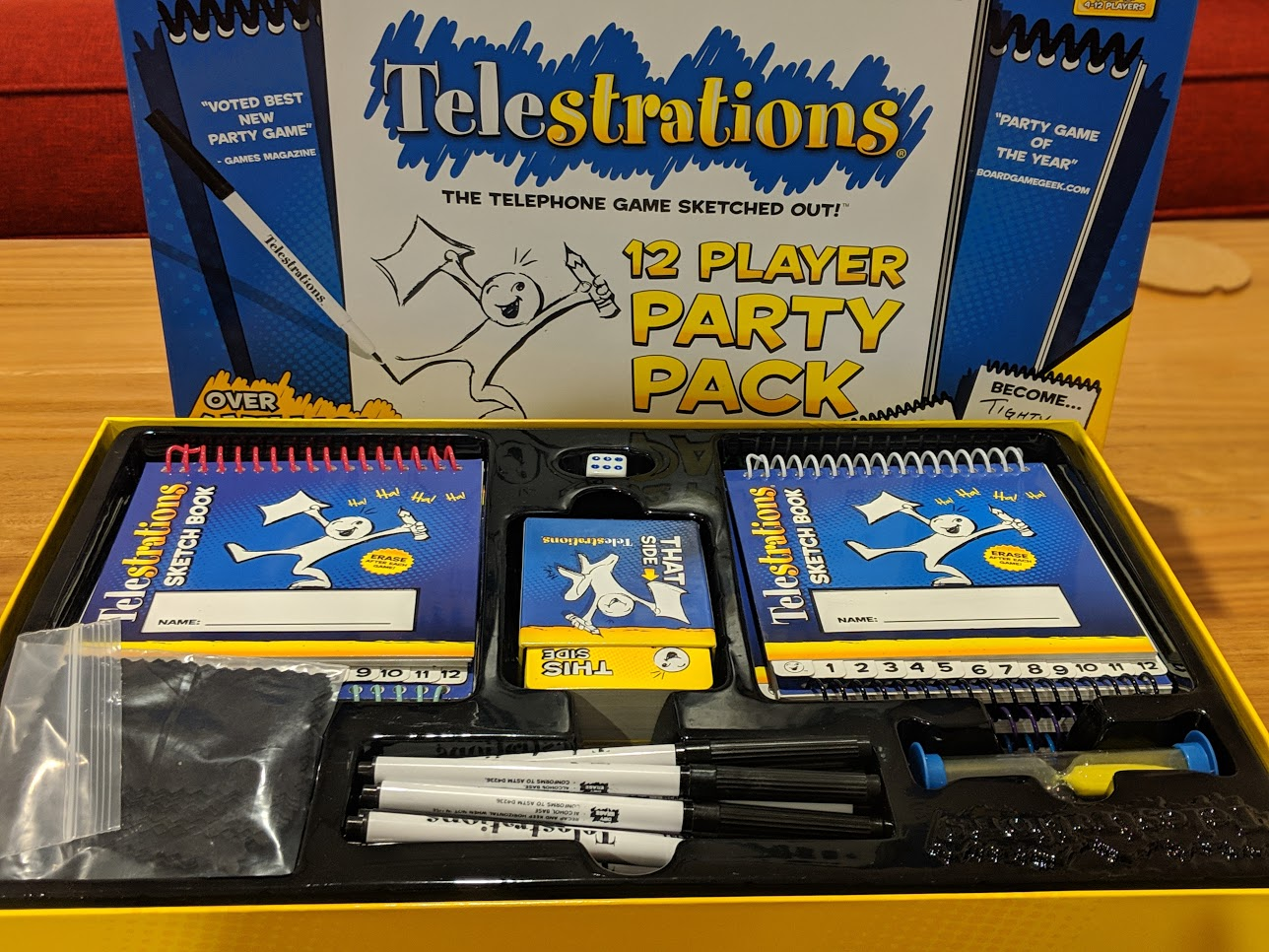 Everything you get in Telestrations 12 Player Party Pack. Including pens, sketch books, timers, and cloths.