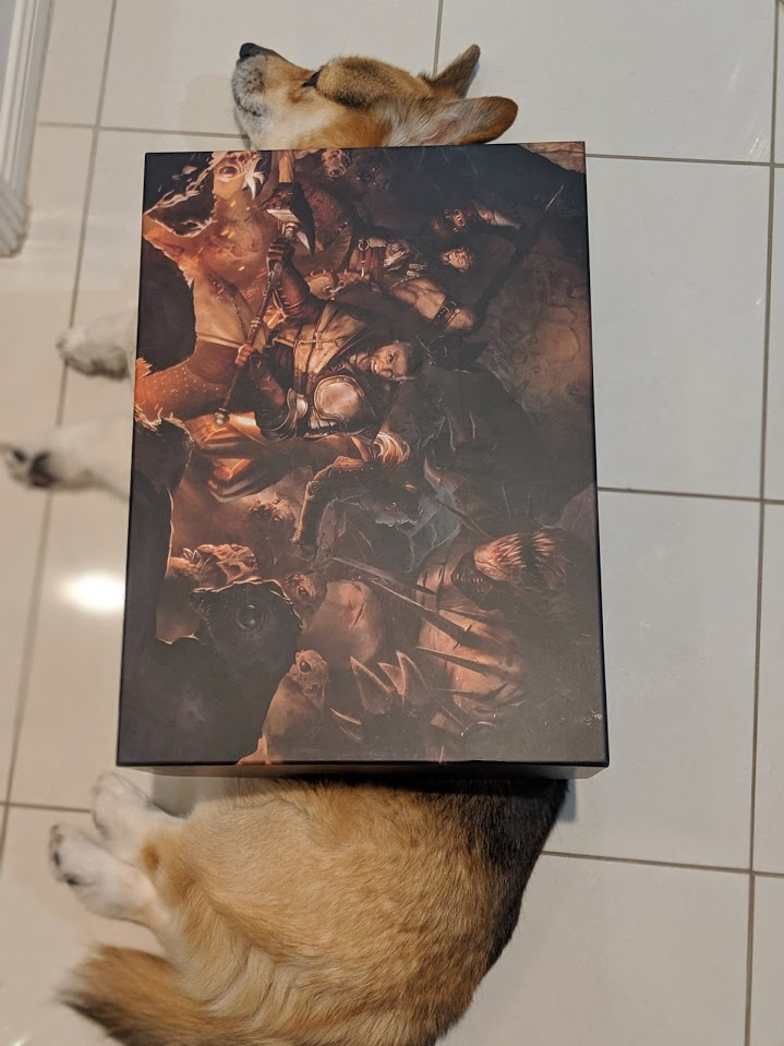 The Claustrophobia 1643 box lying over the top of a corgi. Only the dogs face and rump are seen.