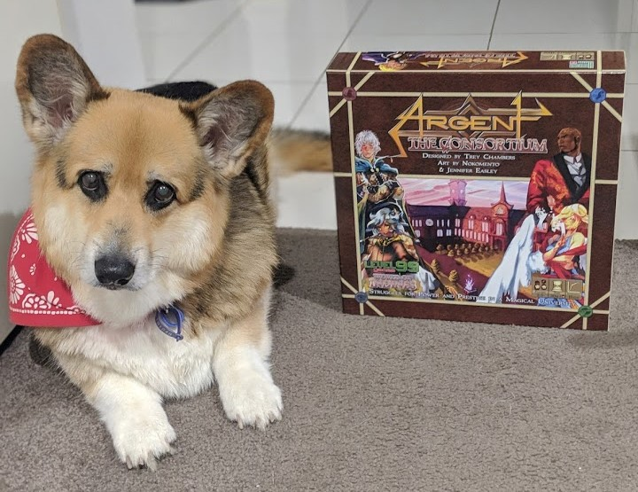 Corgi laying next to the board game Argent the Consortium