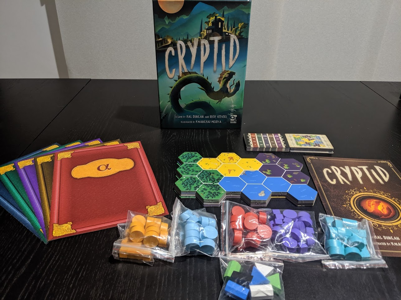 Components of Cryptid laid out on the table.