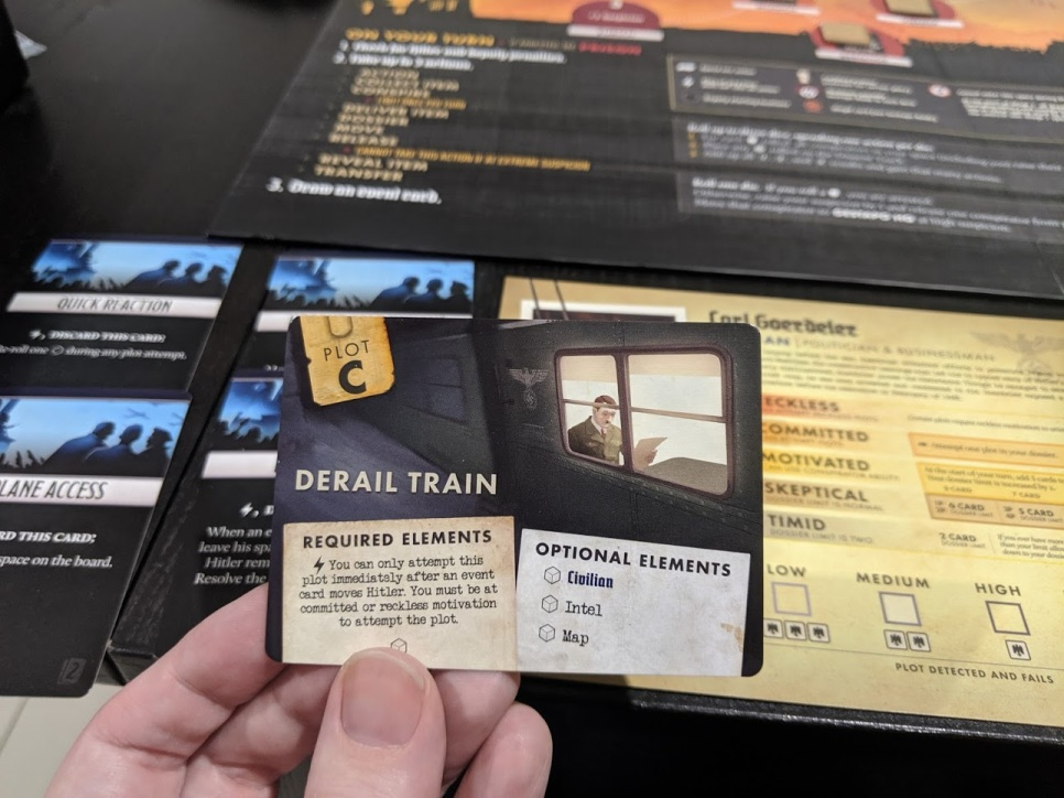 A derail train plot card shows Hitler on a train reading a paper.