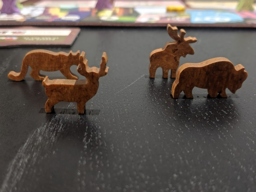 Each animeeple in Parks is uniquely crafted, here you see a cougar, a deer, a moose, and a buffalo.