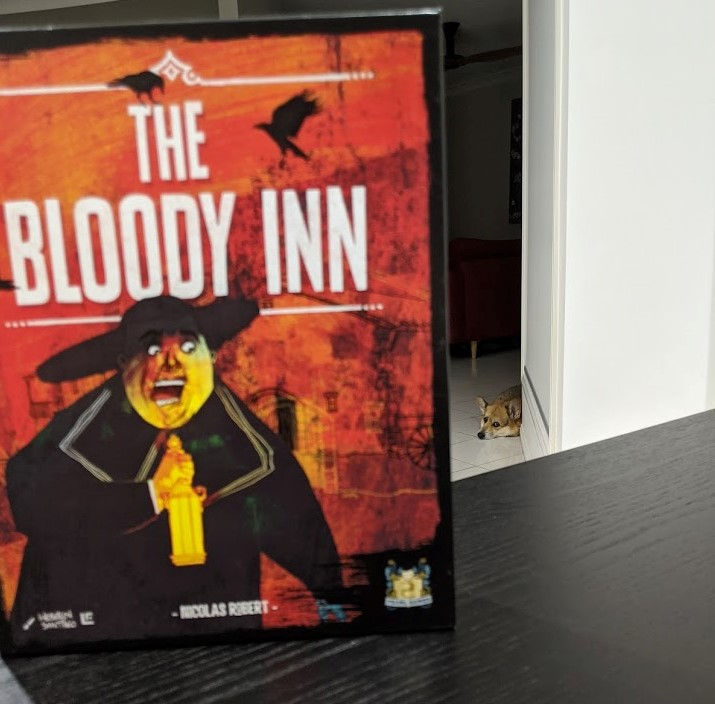 The Bloody Inn box in the foreground, while a cute corgi is laying down in the background looking at the camera.