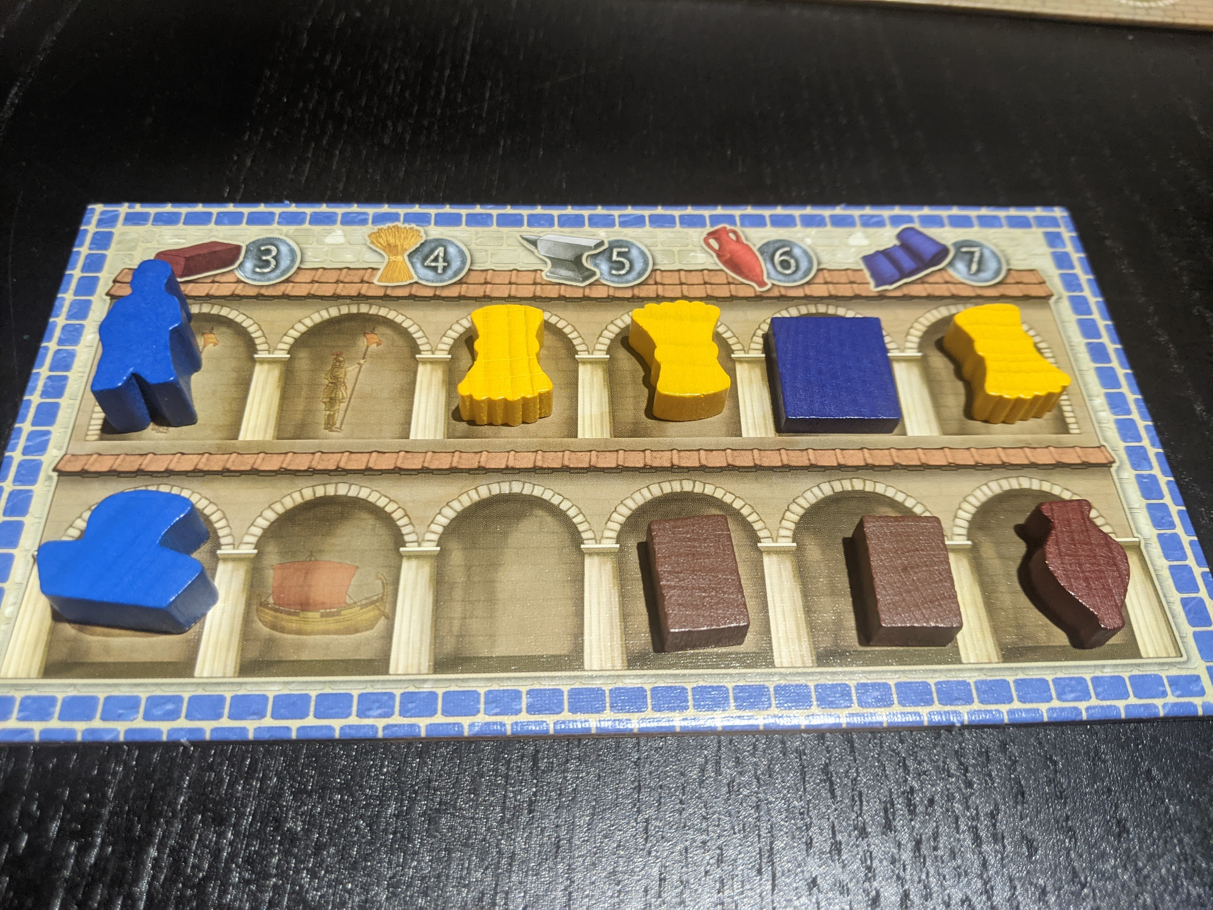Up close shot of wheat, fabric, bricks, wine components on a player board.