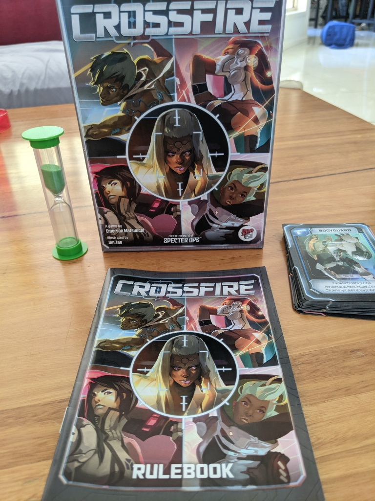 Everything inside the Crossfire box, a green sand timer, a rulebook, and a deck of cards.