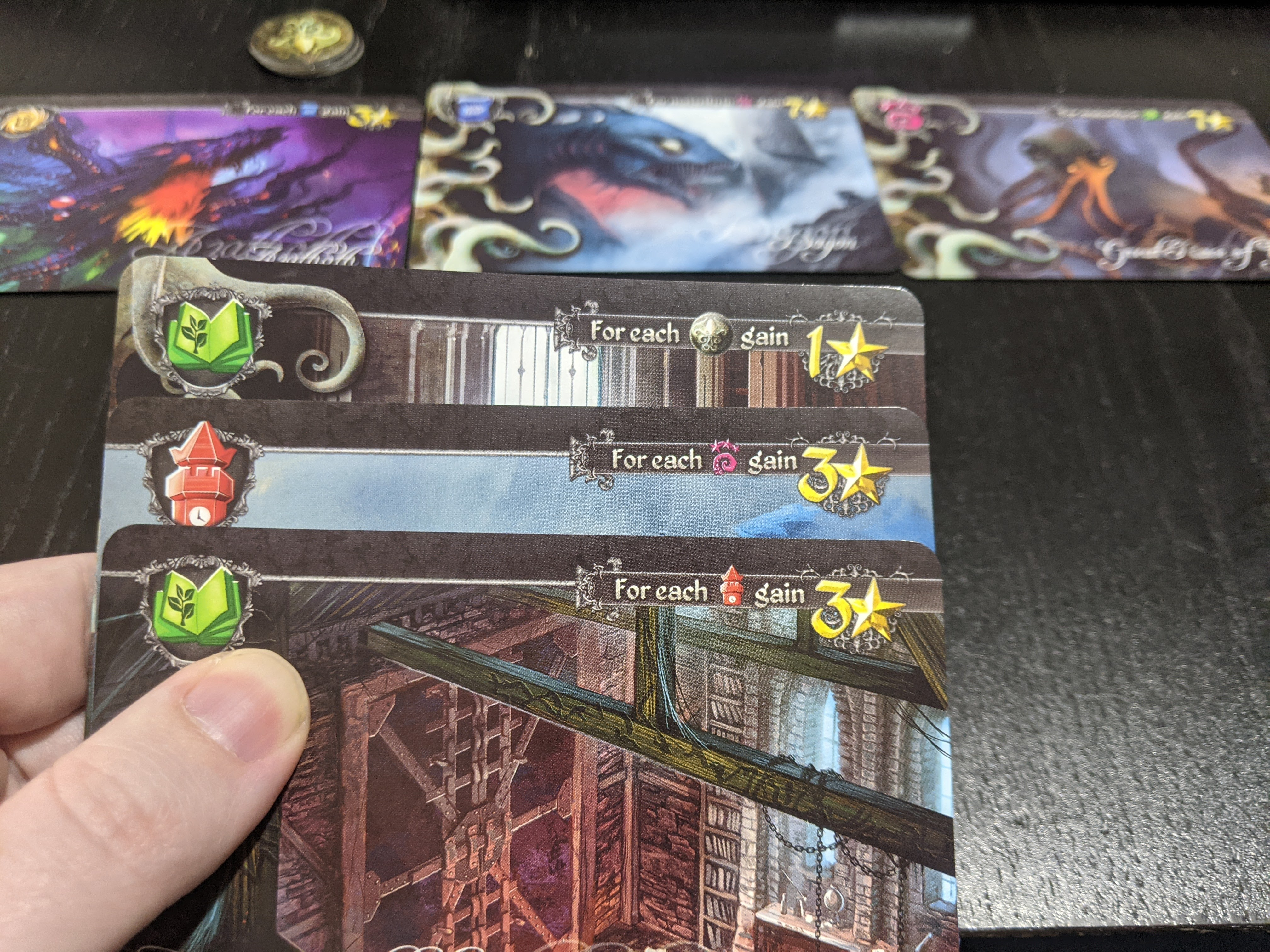 A hand of cards in Tides of Madness, shows three cards in hand, three already on the table, and three madness tokens.
