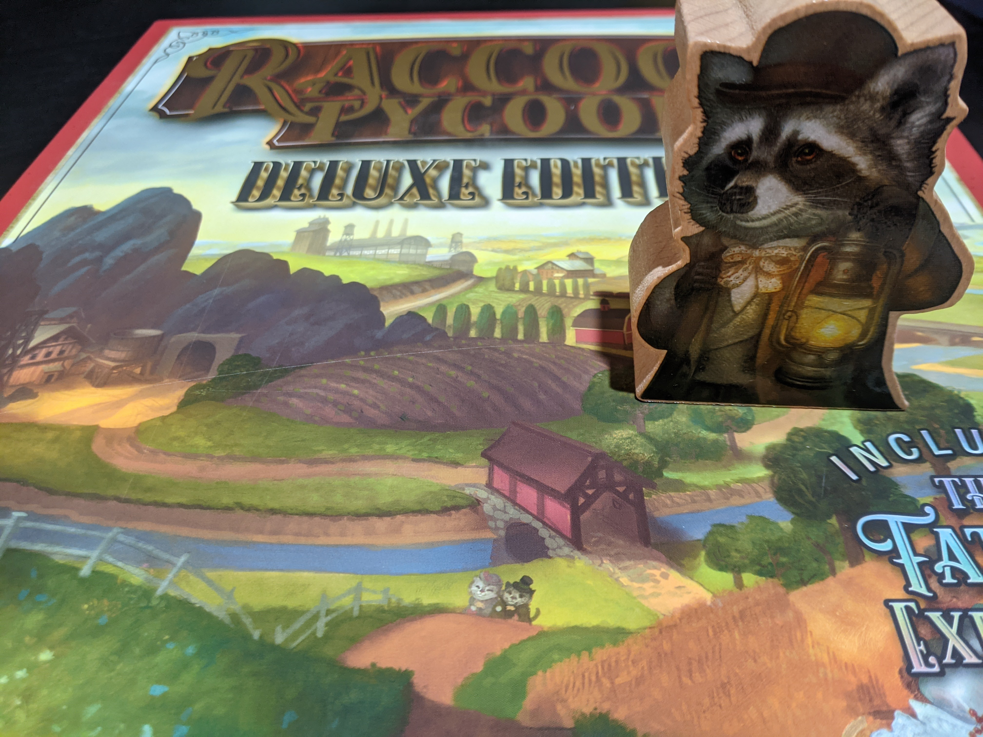 The first player marker is this massive wooden raccoon, sitting on top of the box of Raccoon Tycoon.