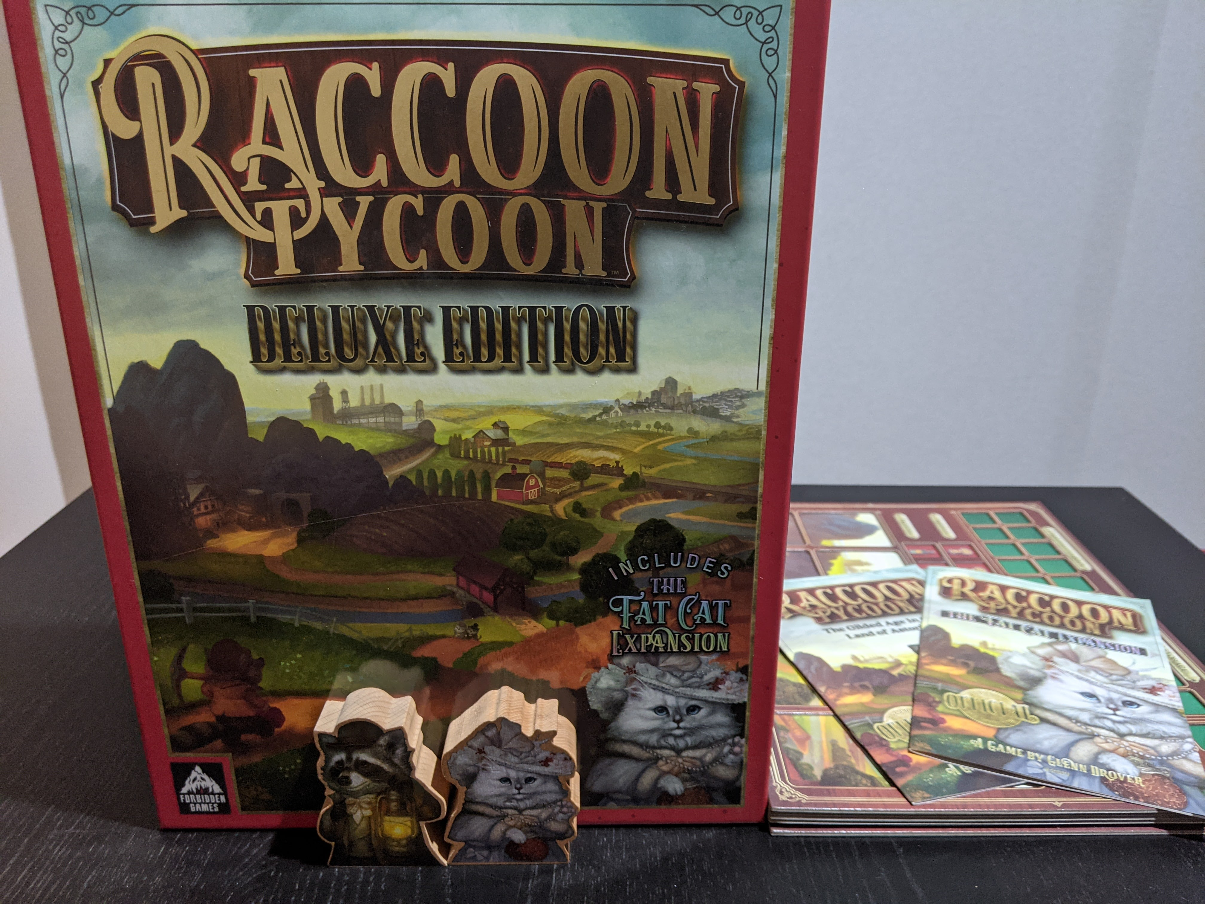 The box of Raccoon Tycoon deluxe addition. Showing off the size of the box, and the first player tokens.