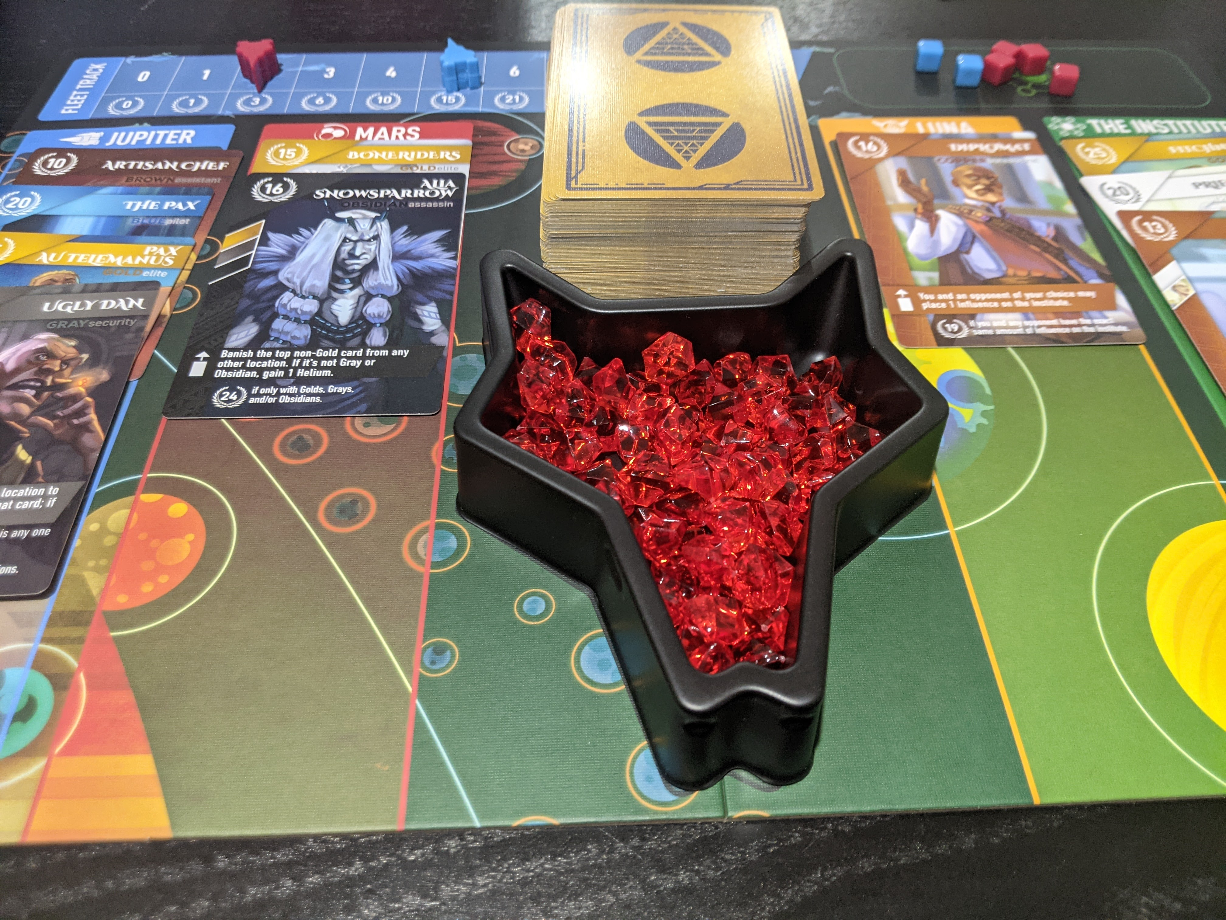 In the middle of a game of Red Rising, the board shows four columns (locations) with cards stacked in each. Front and centre is the container of Helium tokens.