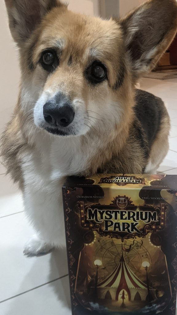Chester the corgi standing behind the Mysterium Park box.